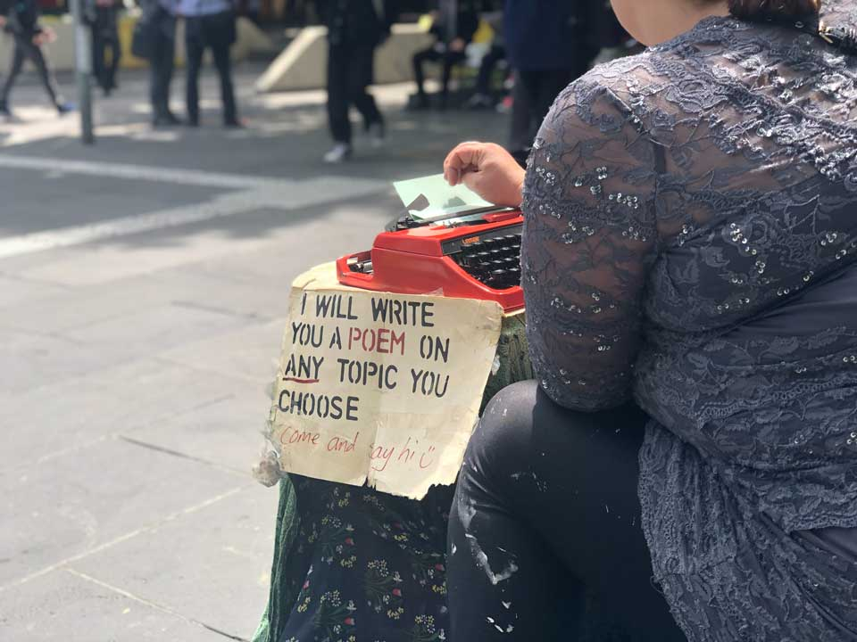 Woman sitting at a typewriter in the street. The sign next to her says 'I will write a poem on any topic you choose'