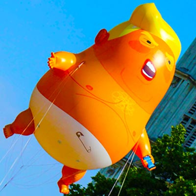 Large balloon of Donald Trump floating with blue sky behind