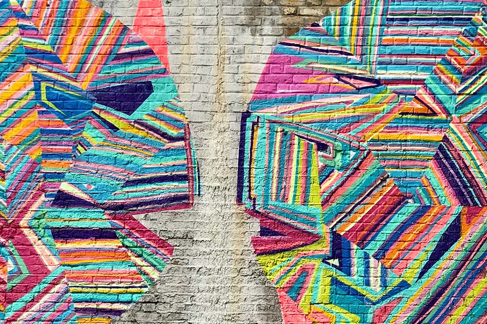 2 multi-coloured heads on a wall
