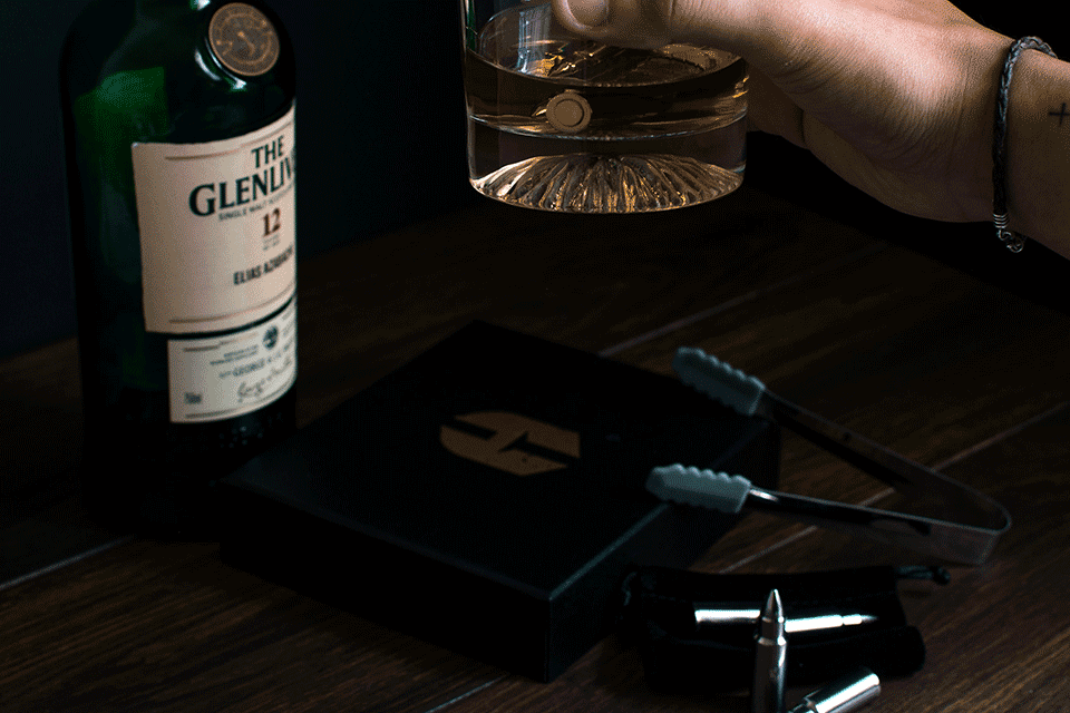 Man holding glass of whiskey containing a bullet, next to bottle of whiskey, bullets and tongs