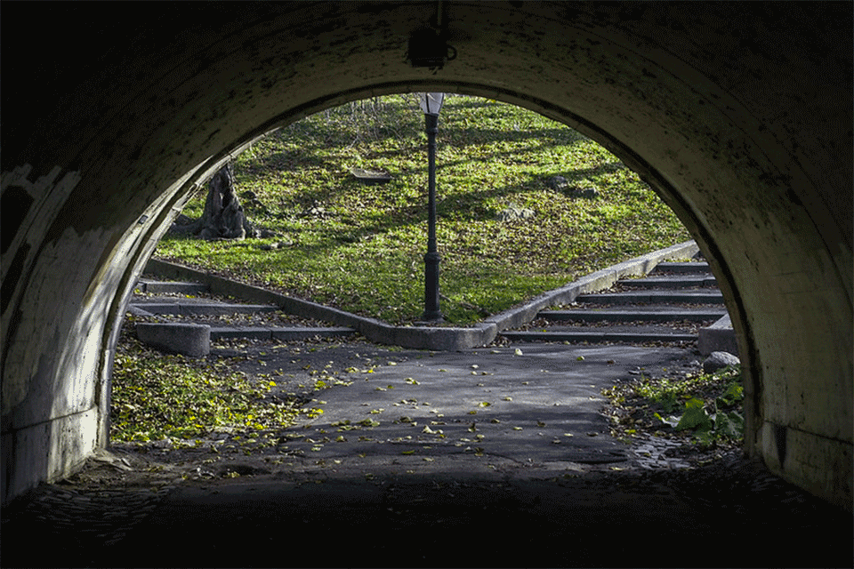 Looking out of tunnel at 2 sets of steps in a park